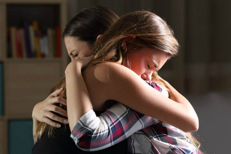Two Friends Hug As Young Woman Experiences Gods Love, Compassion and Forgiveness